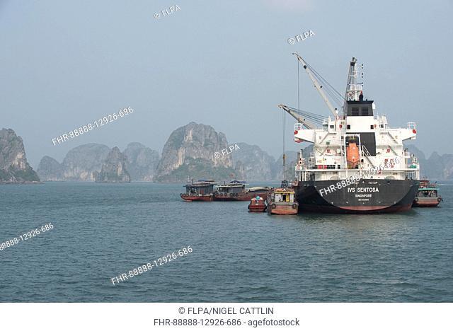 Supply ship loading or unloading cargo from coastal communities, Halong Bay, Vietnam, January