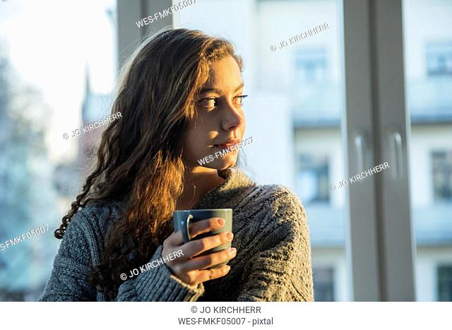 Portrait of teenage girl with coffee mug looking out of window in the evening
