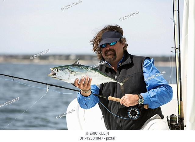 A man holds a fish on a fishing boat with a view of the coast; Cape Cod, Massachusetts, United States of America