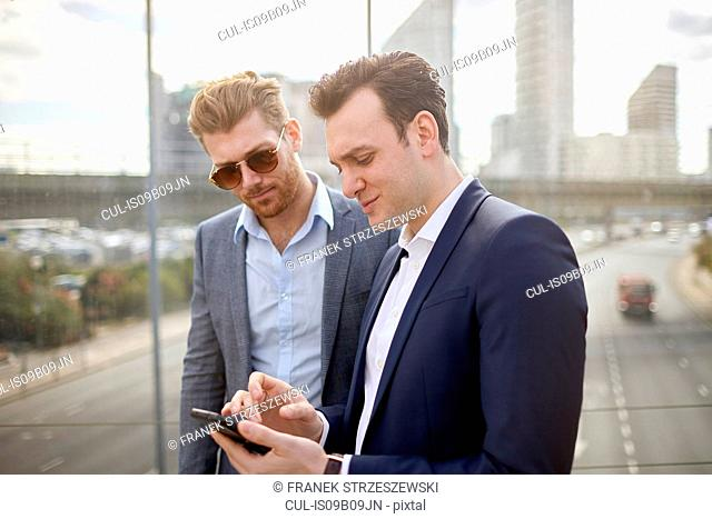Two businessmen on footbridge texting on smartphone, London, UK
