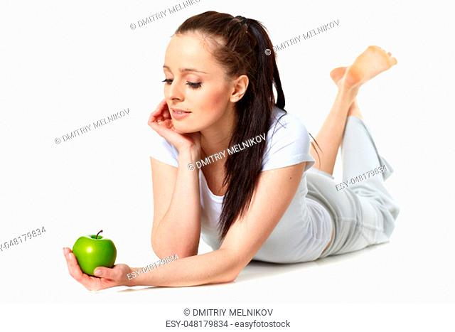 Young beautiful woman with an apple on a white background. Concept of healthy food
