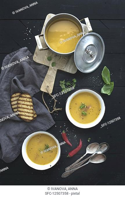 Red lentil soup with spices, herbs, bread in a rustic metal saucepan and bowls, over dark wood backdrop, top view, vertical
