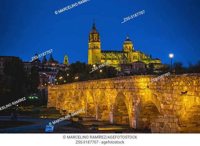 Roman bridge over the river tormes, in the background, the old town of Salamanca at dusk. Salamanca, Castilla y Leon, Spain, Europe