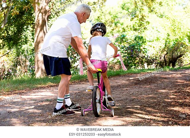 Grandfather teaching his granddaughter how to ride a bicycle