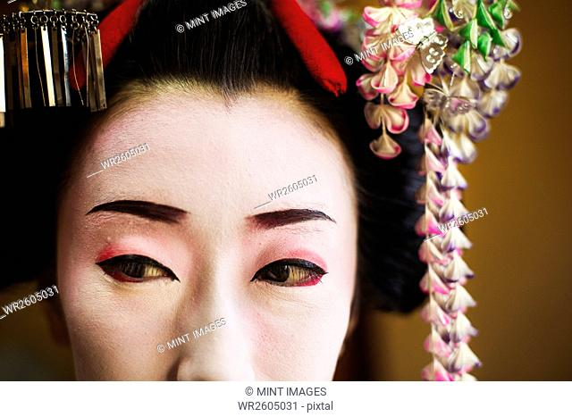A woman made up in traditional geisha style with an elaborate hairstyle and floral hair clips, drawn eyebrows with white face makeup with bright red lips and...