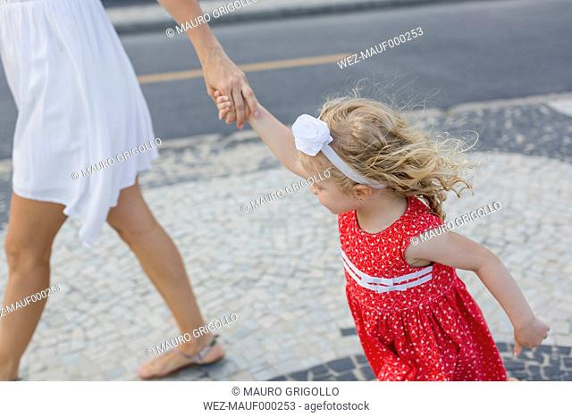 Mother and daughter walking hand in hand