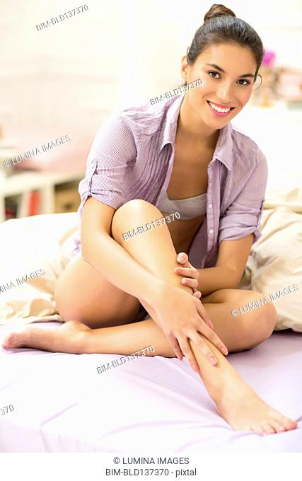 Caucasian woman smiling on bed