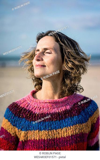 Mature woman enjoying the wind on the beach, portrait