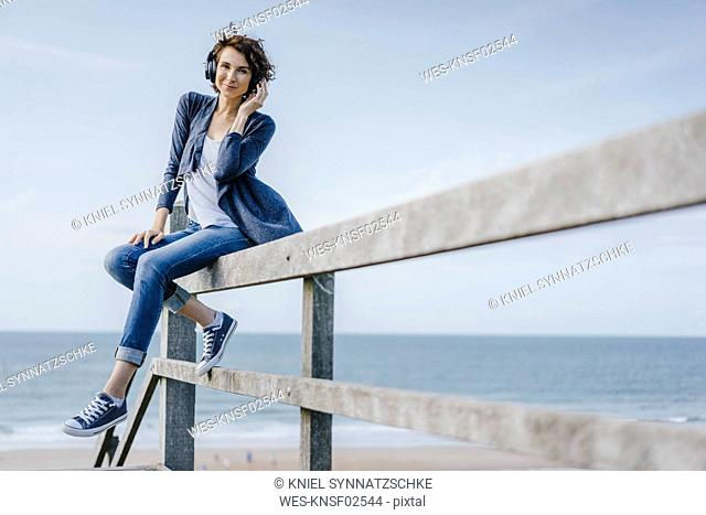 Woman sitting on railing at the beach listening to music