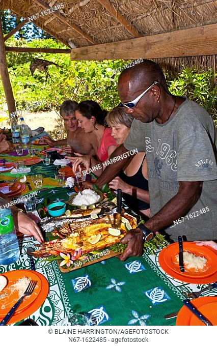 A Kanak Melanesian man serving a seafood lunch that he has just cooked on Brush Island, New Caledonia Barrier Reef off Ile des Pins Isle of Pines, New Caledonia