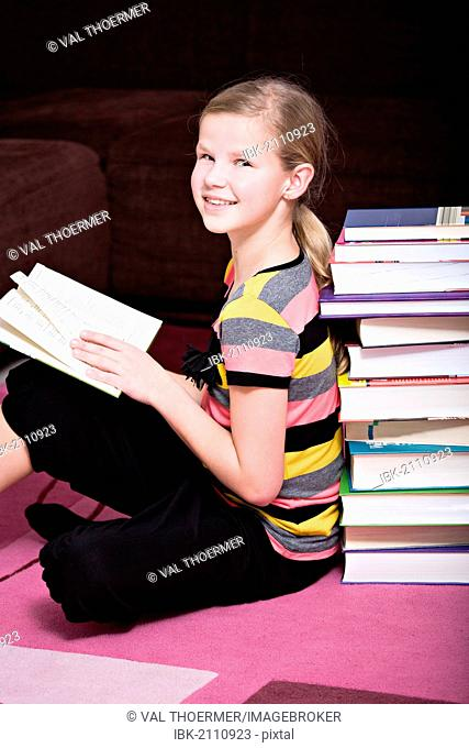 Girl, 11, leaning against a stack of books