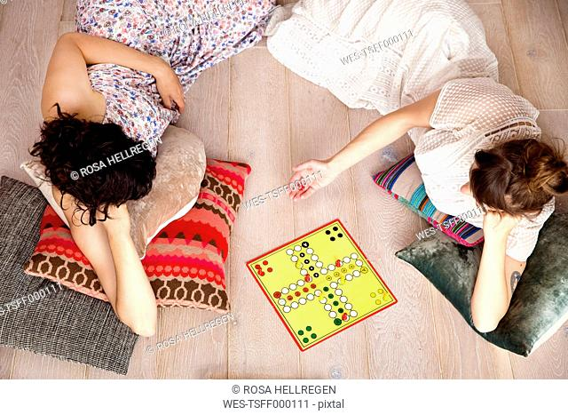 Top view of two best friends lying on the floor at home playing ludo