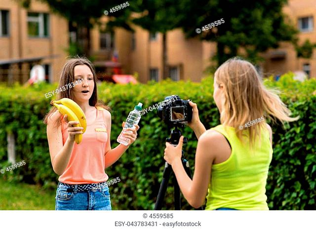 Young girls bloggers, in the summer in the city on nature. Record video on the camera. In her hands holds a bottle of water and two bananas