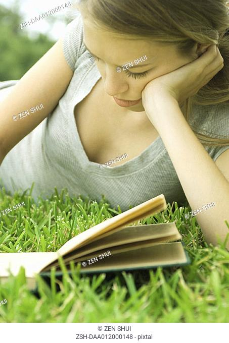 Young woman reclining in grass with book