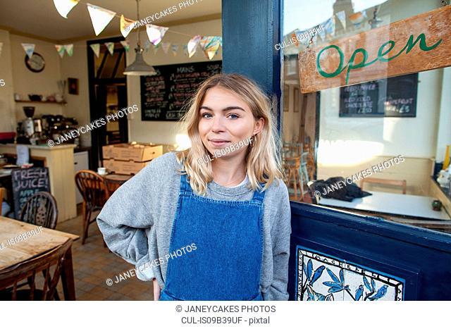 Portrait of young woman standing in doorway of cafe