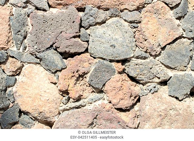 Stone texture background. Close-up of stone wall fragment with colorfull surface as rock wall texture for designer