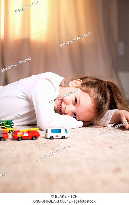 Smiling Girl Portrait on Floor with Toy Cars and Trucks