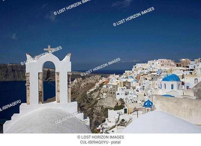 View of white washed church bell tower and town, Oia, Santorini, Cyclades, Greece