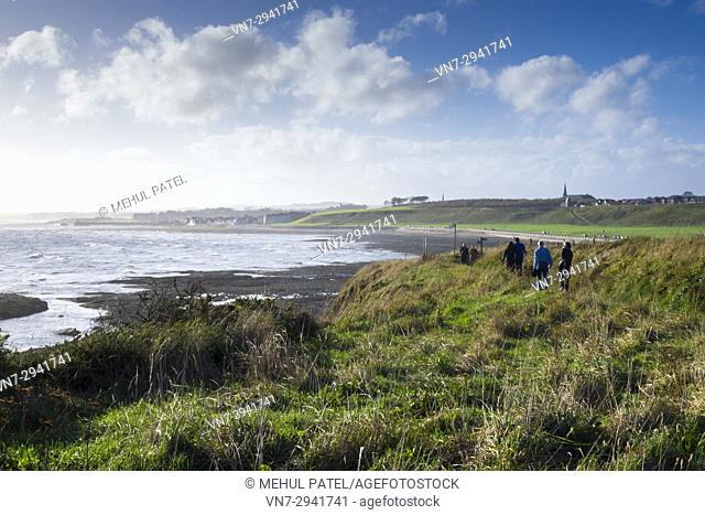People walking along the coastal path of Seaton Cliffs towards the Victoria Park beachfront in Arbroath, Scotland