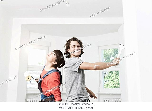 Germany, Cologne, Young couple painting in renovating apartment