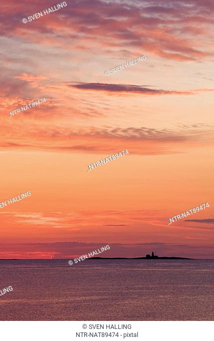 Sunset sky with sea and distant lighthouse