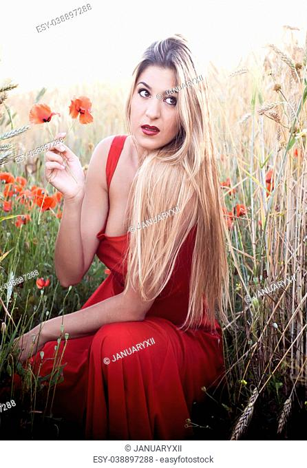 Beautiful blond woman in a wheat field with poppies at sunset backlit