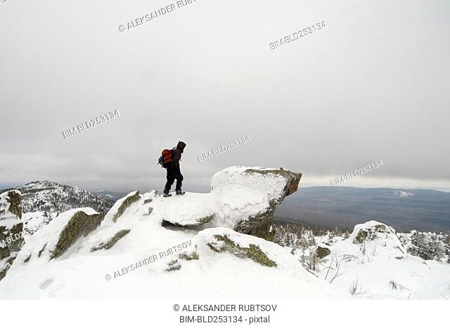Distant Caucasian man standing on mountain in winter