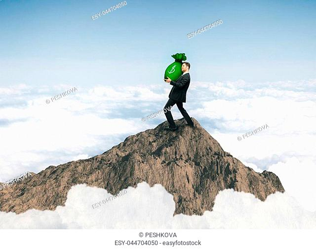 Young businessman standing on mountain top and holding heavy money bag on sky background. Wealth and leadership concept