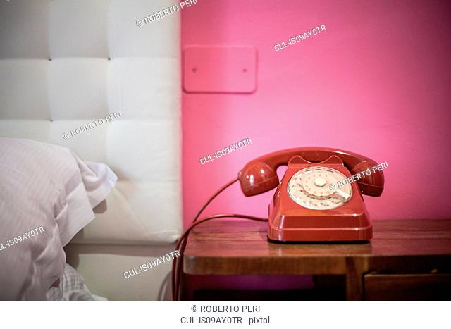 Red rotary telephone on bedside table