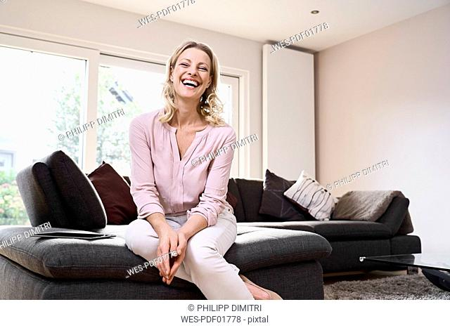 Portrait of laughing woman sitting on couch at home