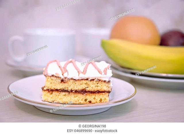 On the table on a plate of delicious cake, next to a Cup of tea and fruit
