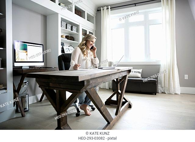Woman working in home office talking on cell phone