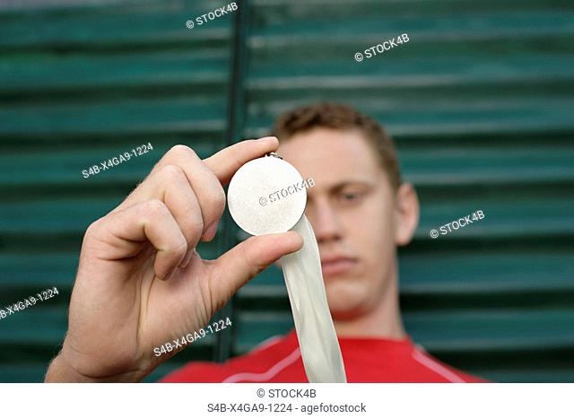 Young man in front of a wall made of corrugated sheet iron holding aup a medal, selective focus
