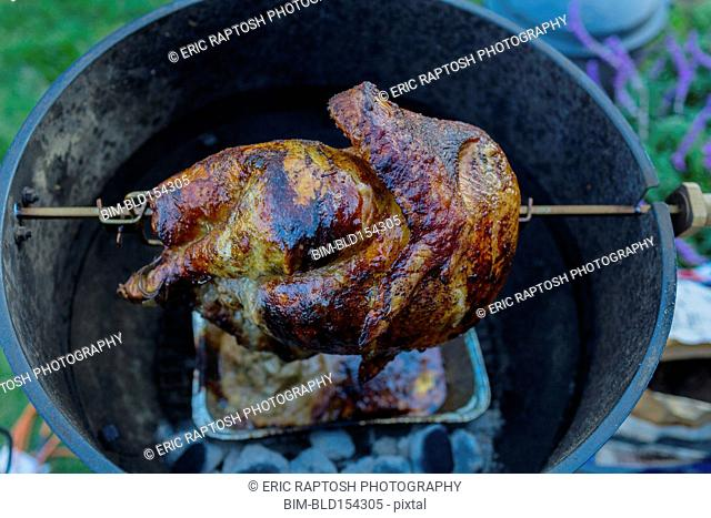 Close up of chicken cooking on rotisserie barbecue