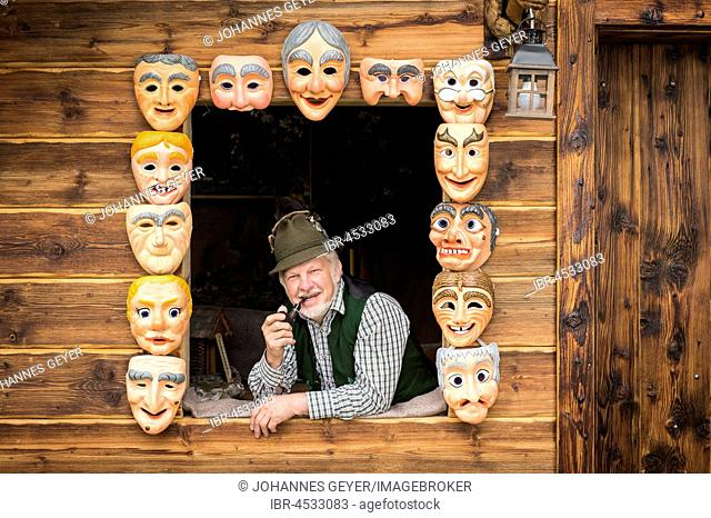 Wooden mask carver in a window, framed by painted wooden masks, wooden mask carving workshop, Bad Aussee, Styria, Austria