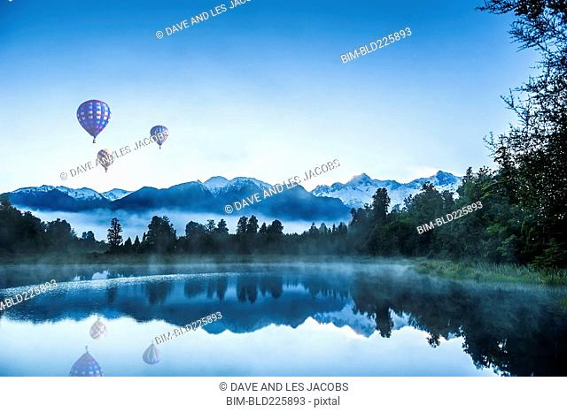 Hot air balloons floating over foggy mountain lake