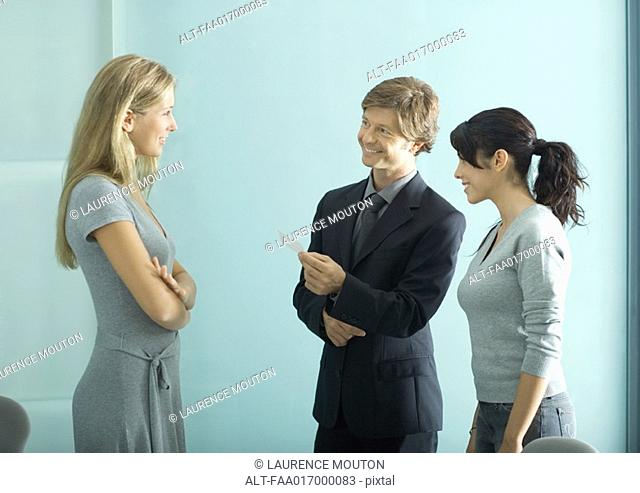 Mature man and teenage girl facing young female professional, man holding business card
