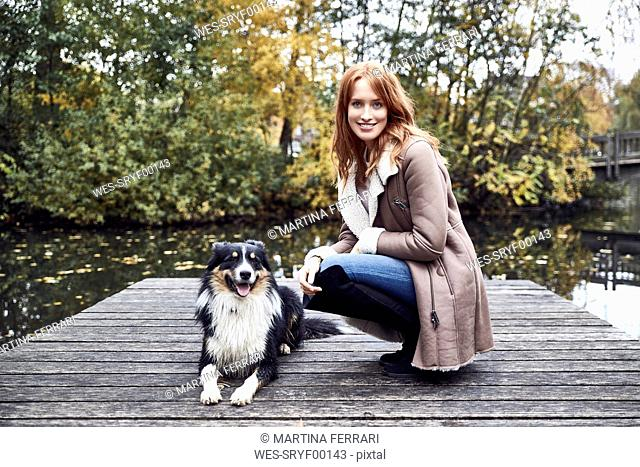 Portrait of smiling woman with her dog on jetty in autumn