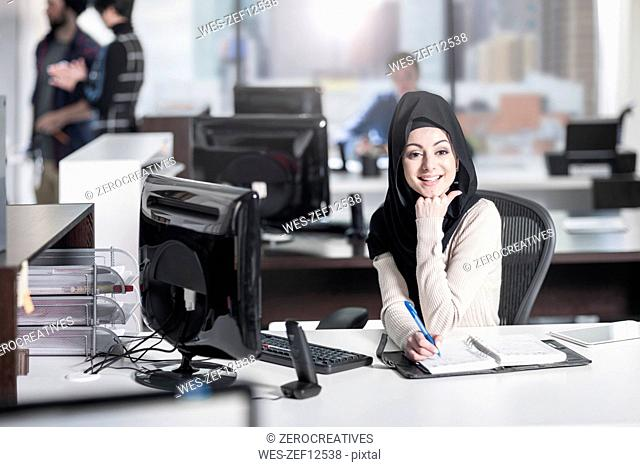 Portrait of smiling young woman wearing hijab in office