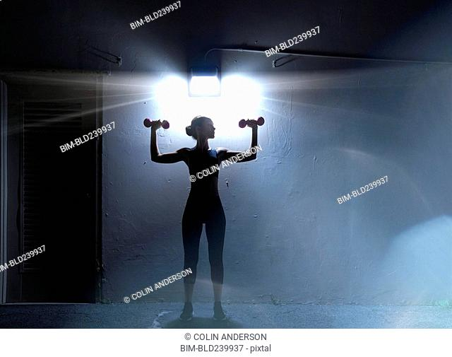 Pacific Islander woman lifting dumbbells under lamp at night