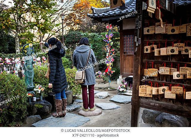 Couple praying. Temple area dedicated to dead unborn children, in Zojoji temple, Tokyo, Japan