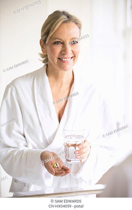 Smiling mature woman in bathrobe taking vitamins at bathroom mirror