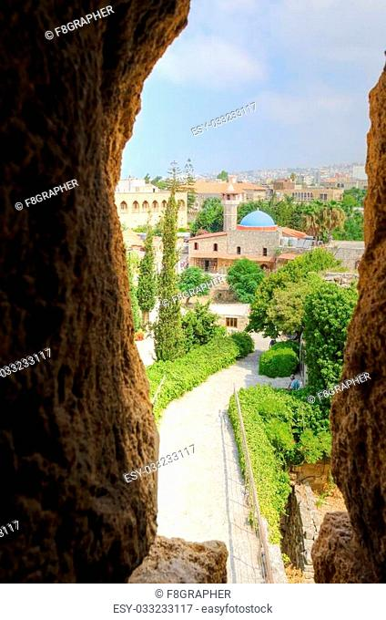 The historic city of Byblos in Lebanon viewed from the arrow loop of the crusaders' castle. A view of the mosque and the path leading to the castle entrance