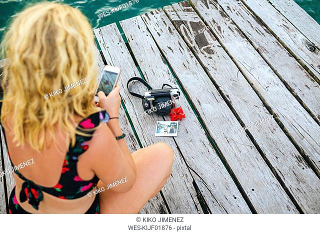 Panama, Bocas del Toro, Woman taking a picture with her smartphone of a camera and instant photographs
