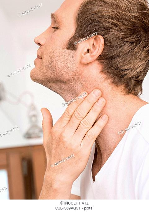 Close up of man in bathroom applying moisturizer to neck