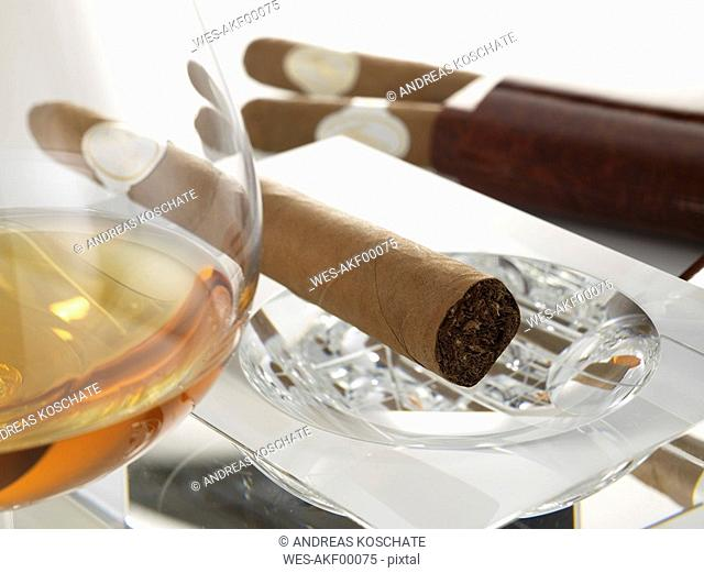 Cigar in ashtray with glass of cognac, close-up