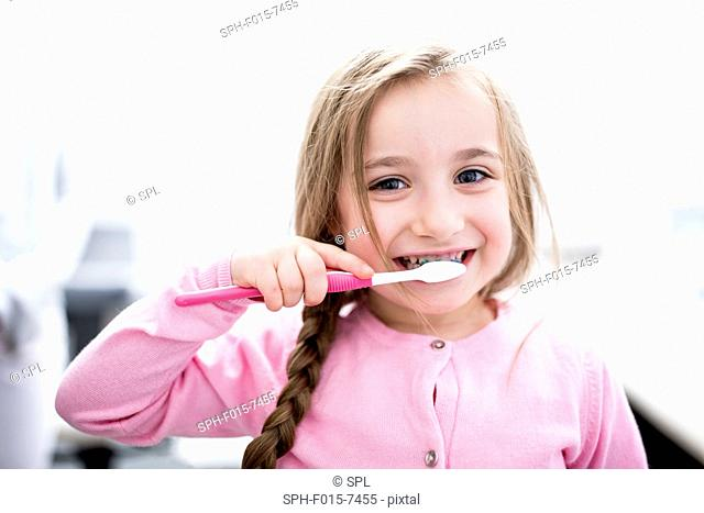 MODEL RELEASED. Girl brushing teeth, portrait, close-up