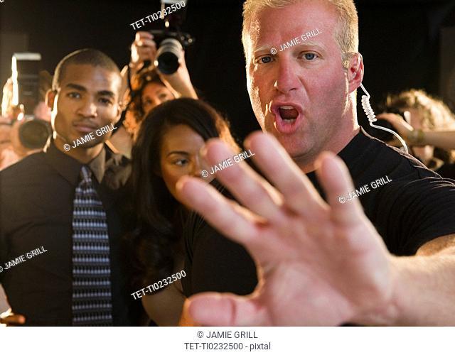 Bouncer shielding celebrity at red carpet event