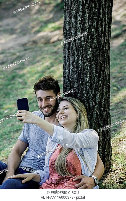 Young couple listening to music and taking selfie with a smartphone