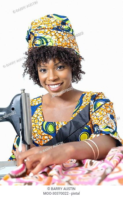 Portrait of an African American woman using sewing machine over gray background